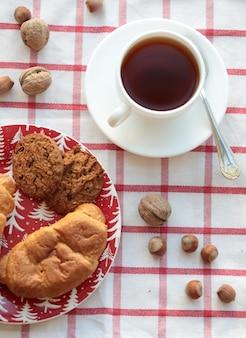 Een kopje thee met noten en gebak op het geruite tafelkleed. bovenaanzicht