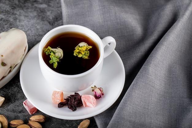 Een kopje thee met noten, turkse lokum en bloesems