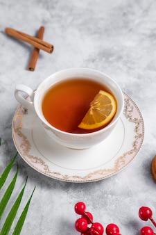Een kopje thee met schijfje citroen en kaneelstokjes.
