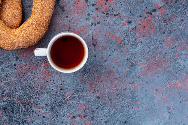 Een kopje thee met sesam bagels op blauwe achtergrond.