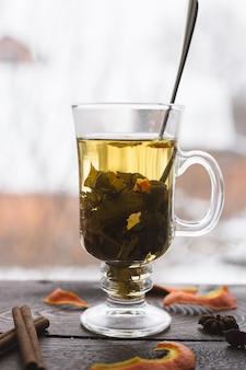 Een kopje thee met sinaasappels en kaneel