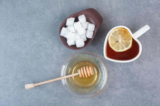 Een kopje thee met suiker en honing op een grijze ondergrond