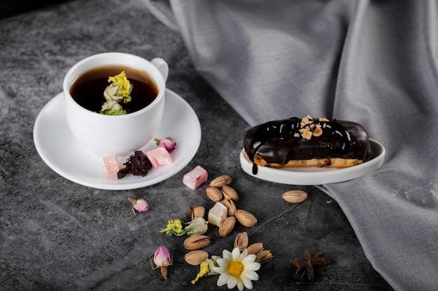 Een kopje thee met turkse lokum, pistachenoten en chocolade-eclair.
