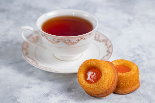 Een kopje thee met zelfgemaakte abrikozenjam thumbprint cookies.