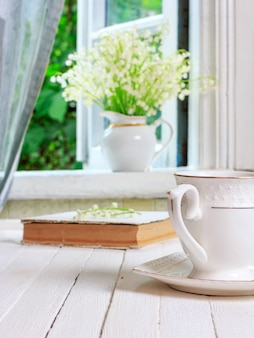 Een kopje thee of koffie en een boek op een witte houten tafel en een boeket lelietje-van-dalenbloemen