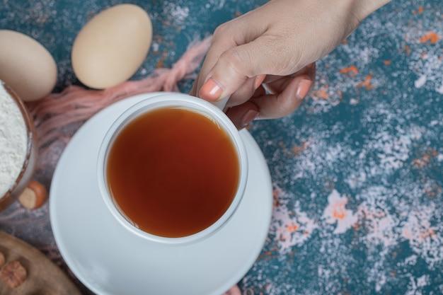 Een kopje thee op een blauwe getextureerde tafel.