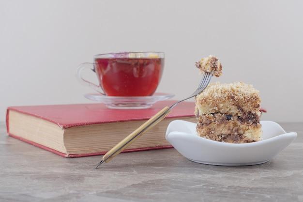 Een kopje thee op een boek naast een kleine portie cake op marmer