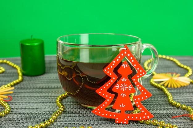 Een kopje thee op een groene achtergrond met een kerstboom en een kaars.