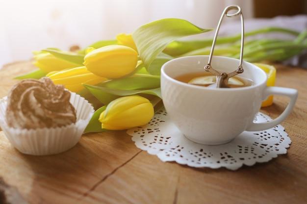 Een kopje thee op houten tafel met marshmallow en gele tulpen. ontbijt op bed
