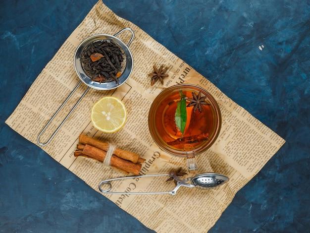 Een kopje thee op krant met kaneel, citroen en een theezeefje