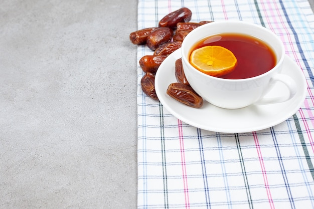 Een kopje thee op schotel naast dadels op handdoek op marmeren achtergrond.