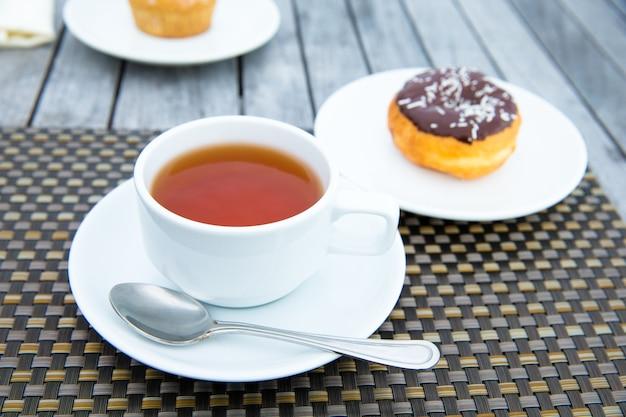 Een kopje thee op tafel met de zee op de achtergrond