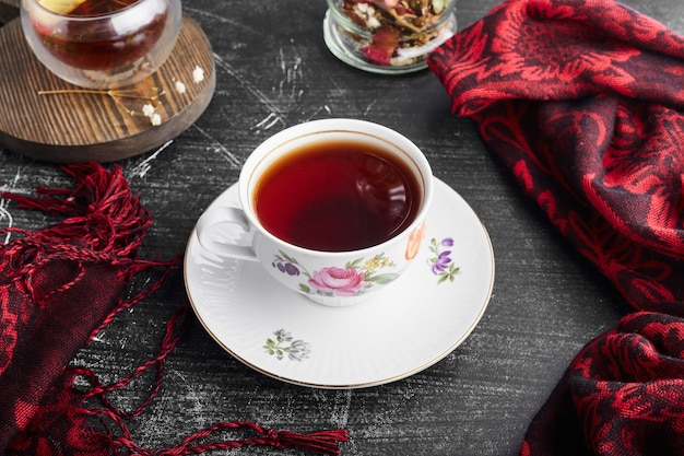 Een kopje thee op zwarte ondergrond.