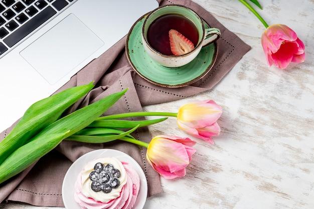 Een kopje thee, tulpen en een taart naast een laptop op tafel.