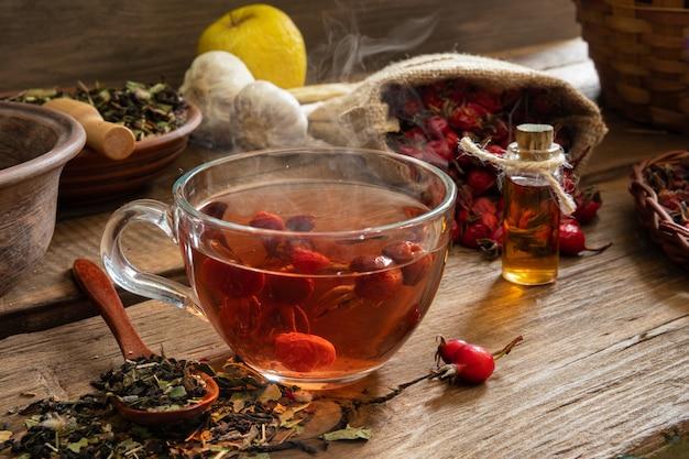 Een kopje thee van wilde roos nuttig voor de gezondheid op een houten achtergrond. dogrose fruit in een canvas tas.