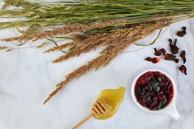 Een kopje verfrissende fruithibiscusthee met munt en honingstokje, een boeket wilde kruiden op een lichte tafel. een verfrissend drankje in de zomerse hitte