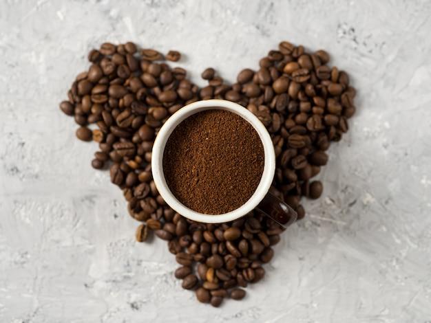 Een kopje vers gemalen koffie op de tafel met koffiebonen in de vorm van een hart