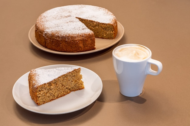 Een kopje verse cappuccino en een fluitje van een cent gemaakt van amandelen en droog brood (antica torta alle mandorle e pane)