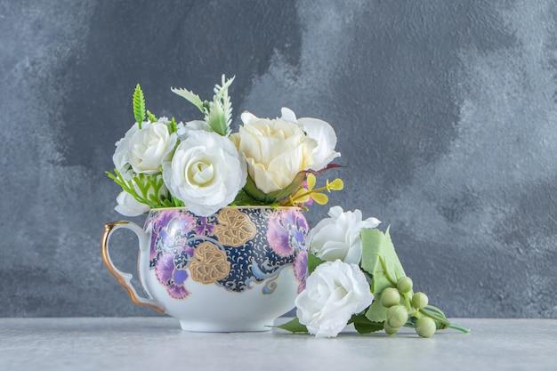 Een kopje verse witte bloemen, op de witte achtergrond.