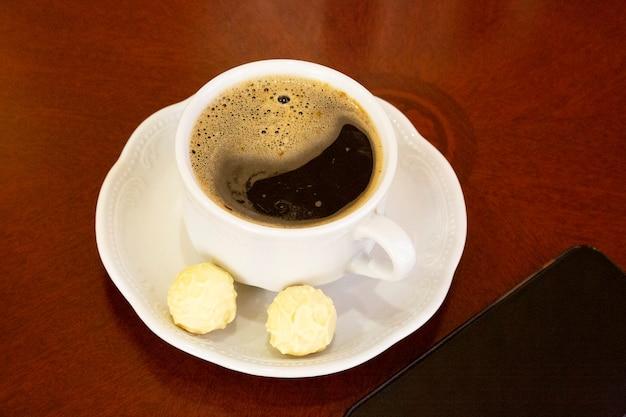 Een kopje witte koffie en ronde snoepjes op een schotel op een houten tafel, er is een smartphone in de buurt