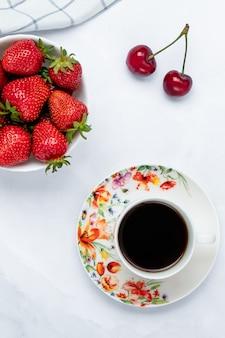 Een kopje zwarte koffie en aardbeien op een witte tafel