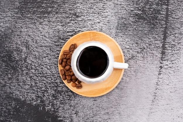 Een kopje zwarte koffie en bonen koffiekopje op zwart