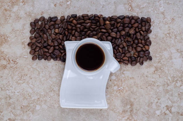 Een kopje zwarte koffie en een keurige stapel koffiebonen