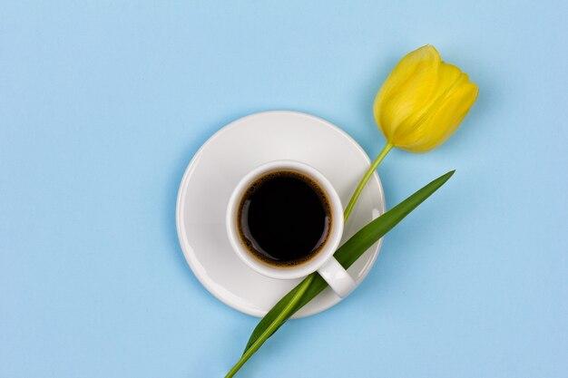 Een kopje zwarte koffie met een gele tulpenbloem op een blauwe achtergrond bovenaanzicht