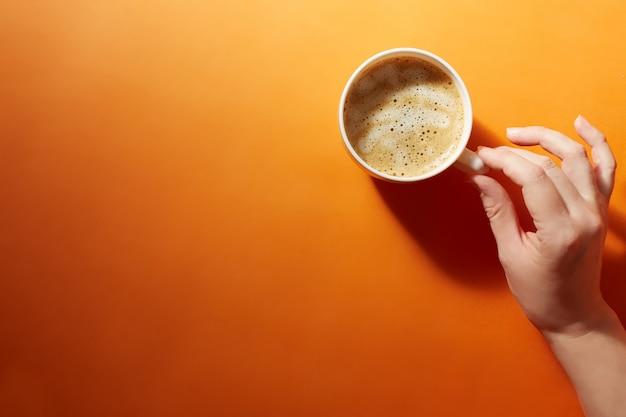 Een kopje zwarte koffie met een vrouwelijke hand op een fel oranje achtergrond. minimalisme, bovenaanzicht. copyspace