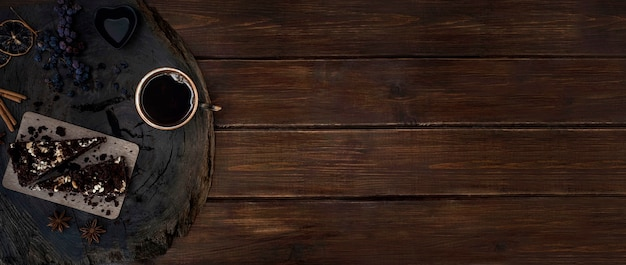 Een kopje zwarte koffie met stukjes chocoladetaart op een houten gebarsten eikenhouten snede. banner met kopie ruimte