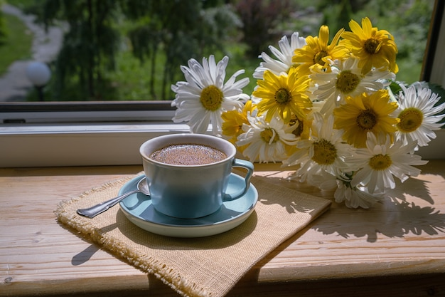 Een kopje zwarte koffie op de vensterbank onder de stralen van de zon, en prachtige bloemen.