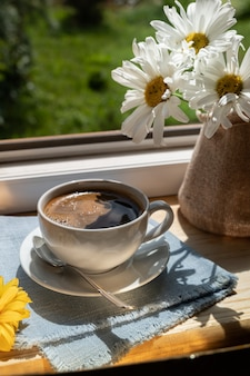 Een kopje zwarte koffie op de vensterbank onder de stralen van de zon, naast prachtige bloemen, verticaal schot.