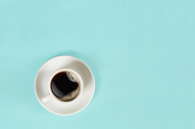 Een kopje zwarte koffie op een blauwe achtergrondweergave van bovenaf