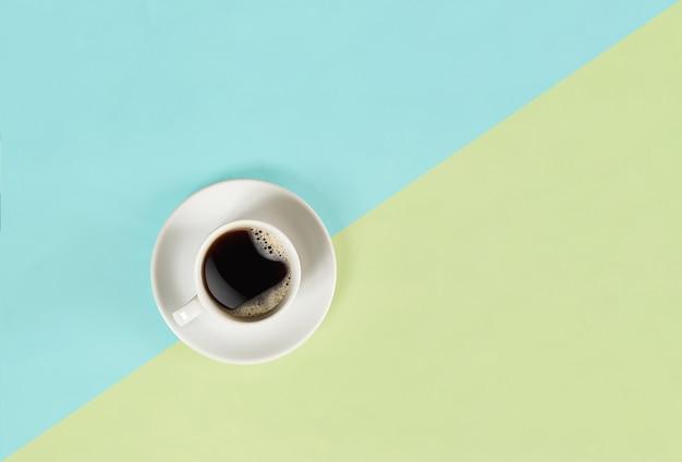 Een kopje zwarte koffie op een blauwe en gele achtergrondweergave van bovenaf