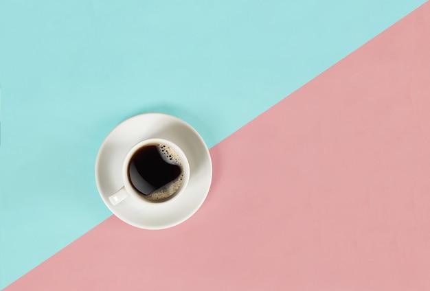 Een kopje zwarte koffie op een blauwe en roze achtergrondweergave van bovenaf