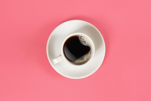 Een kopje zwarte koffie op een roze achtergrondweergave van bovenaf