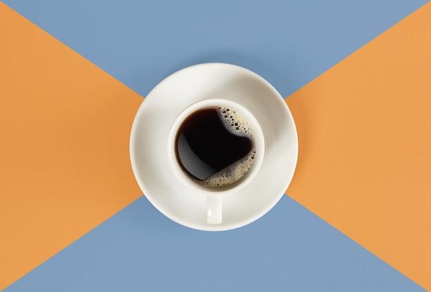 Een kopje zwarte koffie op oranje en blauwe achtergrondweergave van bovenaf