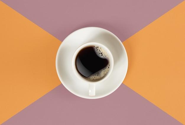 Een kopje zwarte koffie op oranje en rode achtergrondweergave van bovenaf