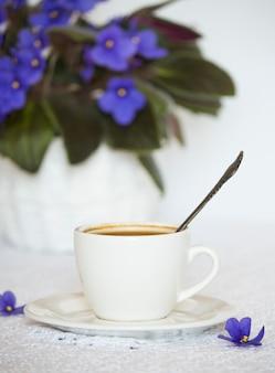 Een kopje zwarte koffie op tafel met een zelfgemaakte violette bloem.