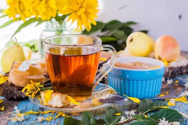 Een kopje zwarte thee en jam van peren in een kom