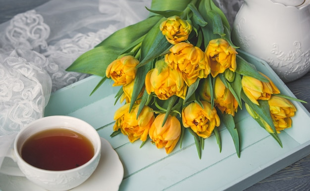 Een kopje zwarte thee met een bos gele tulpen vergezeld