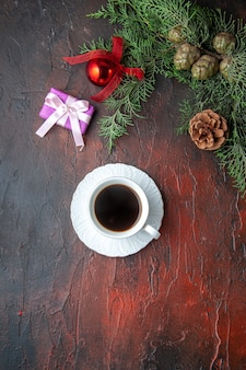 Een kopje zwarte thee spar takken decoratie accessoires en cadeau op donkere achtergrond