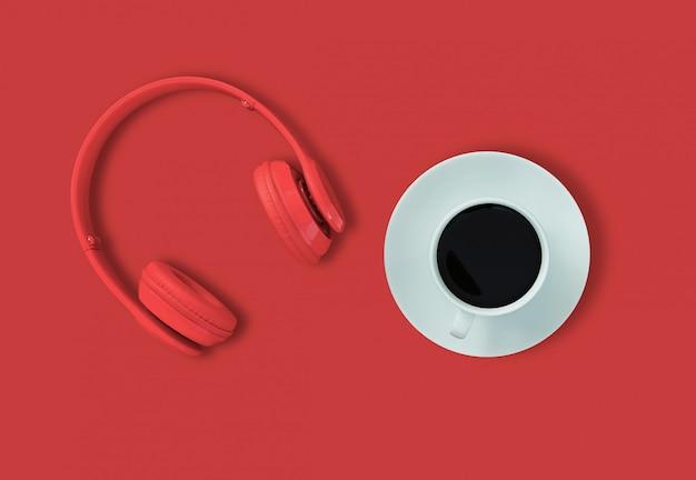 Een koptelefoon, bovenaanzicht van koptelefoon en zwarte koffiekopje op rode tafel