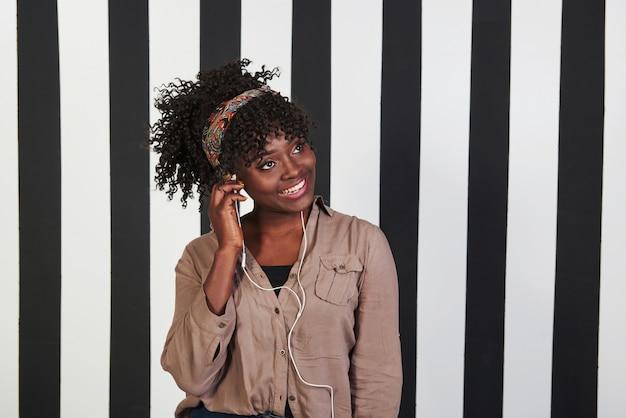 Een koptelefoon in het oor steken en mijn muziek verbazen. glimlachte afro-amerikaanse meisje staat in de studio met verticale witte en zwarte lijnen op de achtergrond
