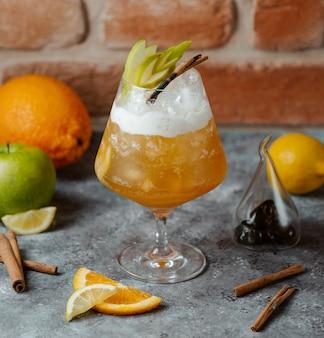 Een koud drankje van citroen en sinaasappelsap met ijsblokjes en plakjes appel erin