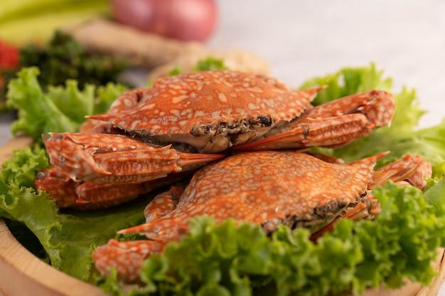 Een krab wordt gekookt op sla in een schotel.