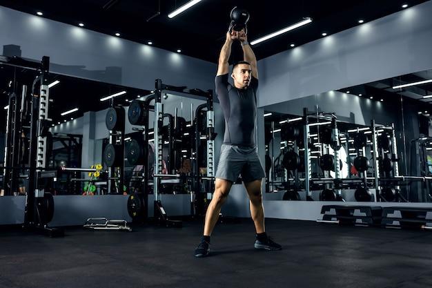 Een krachtige man tilt met krachtige bewegingen een kettlebell boven zijn hoofd in het fitnesscentrum. het concept van functionele cross-fit training. energie boost