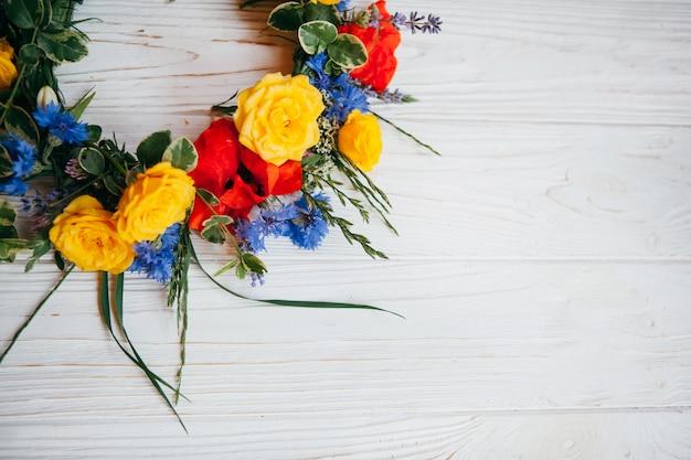 Een krans van rode klaproosbloemen, rozen en blauwe veldbloemen