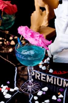 Een kristal lang glas met blauwe lagune gegarneerd met roze zoete katoen