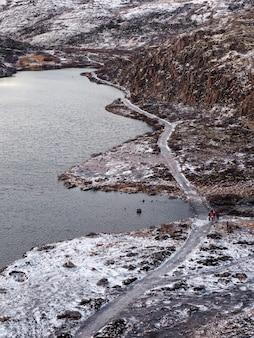Een kronkelend bergpad tussen de besneeuwde arctische heuvels.
